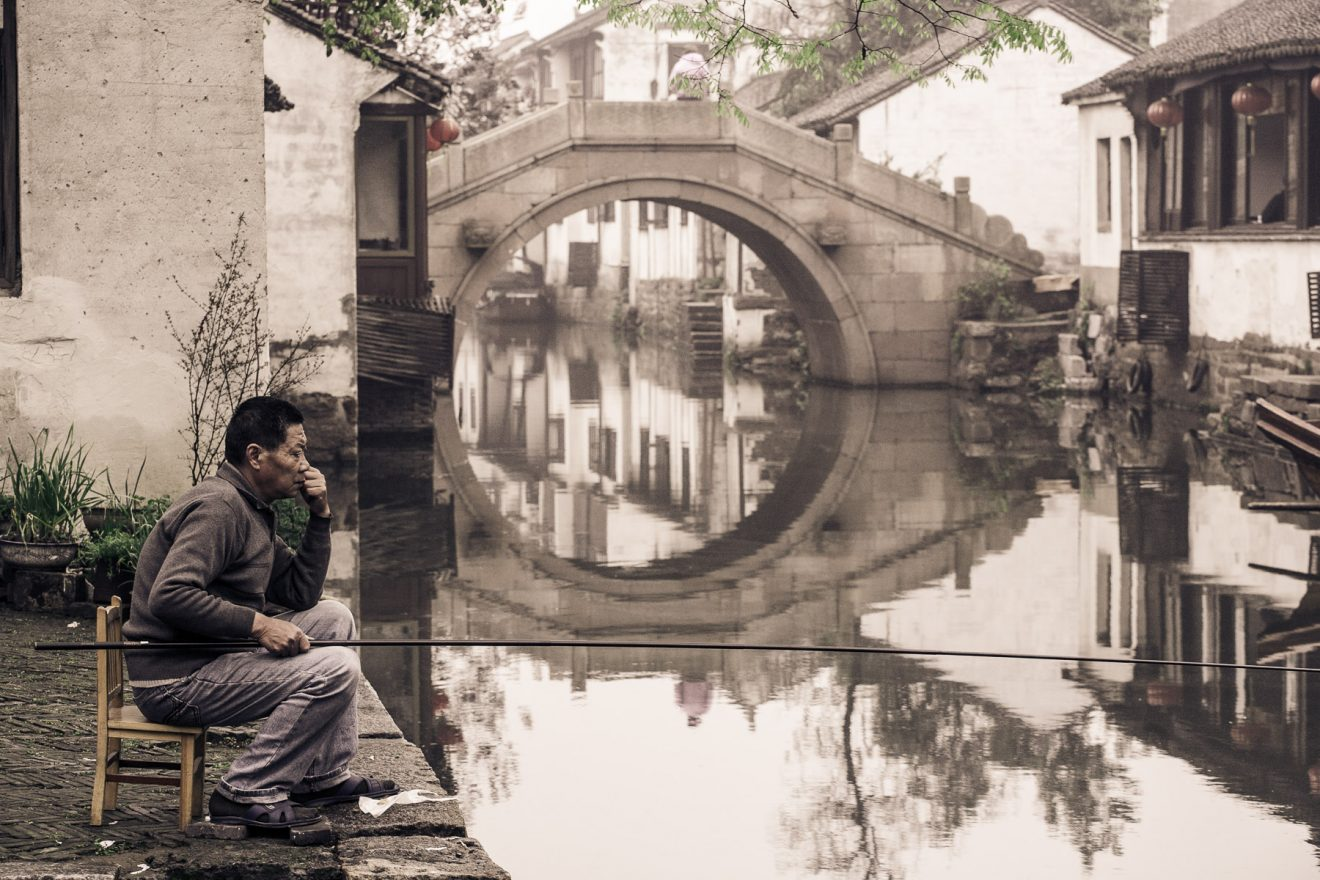 Man fishing at a canal in Zhouzhuang, China
