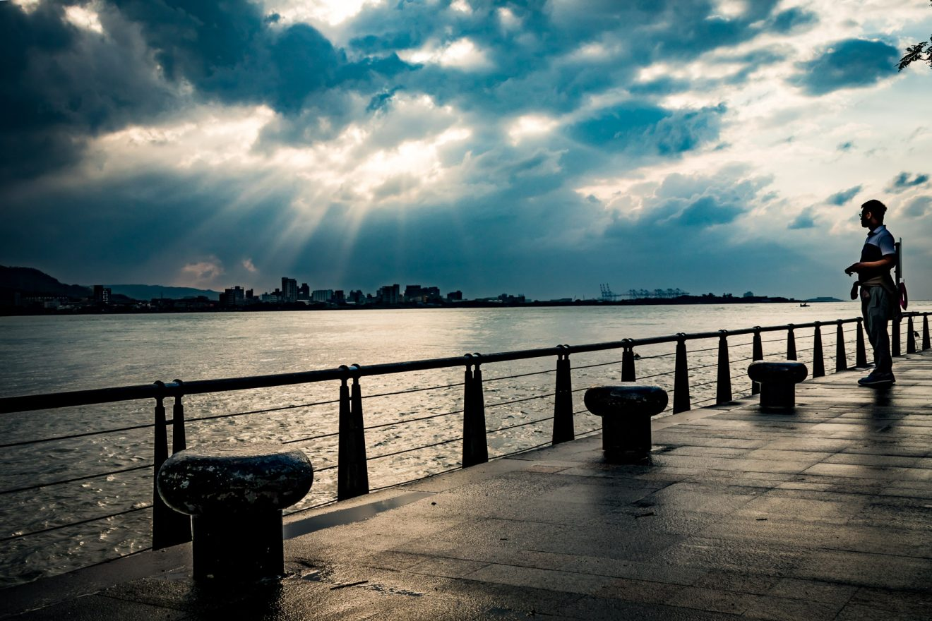 Man observing sea and cloudy sky, shortly before sunset. Tamsui, Taipei.