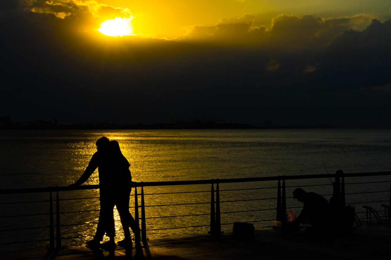 Couple observing sunset at sea in Tamsui / Taiwan.