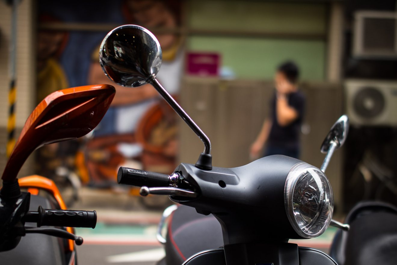 Motorcycle steering wheel, guy in the background. Taipei / Taiwan, 2017.