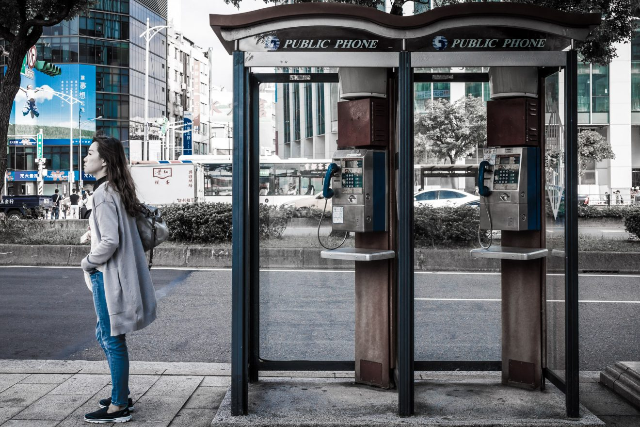 Woman waiting near phone booths