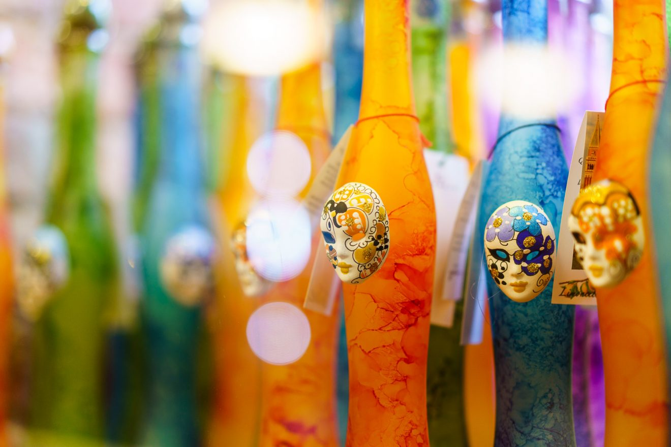 Glass tubes decorated with mini Venetian masques in a Venetian cafe window.