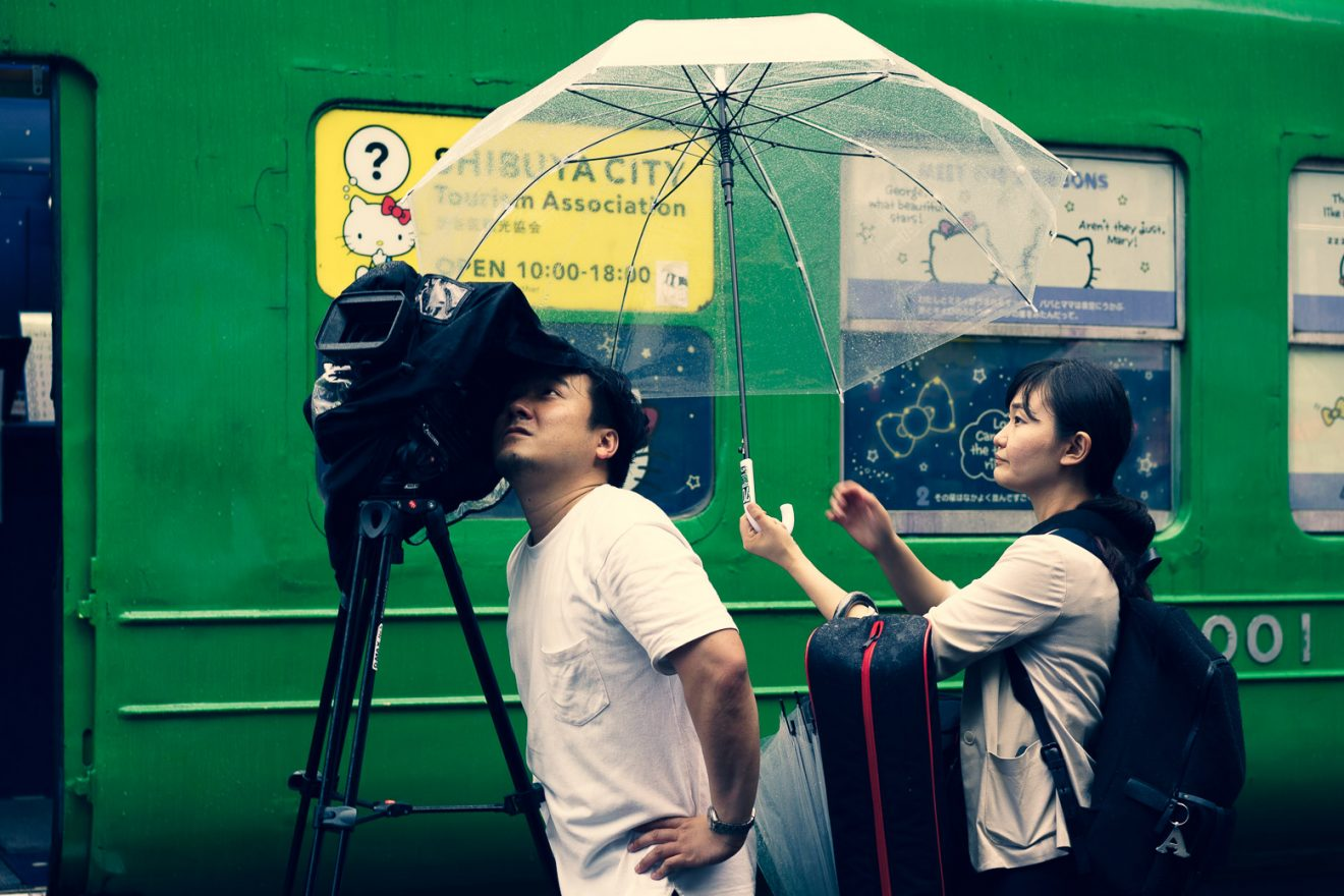 Man looking through film camera on a tripod, woman is holding up umbrella to shield him from rain, both are next to a green bus