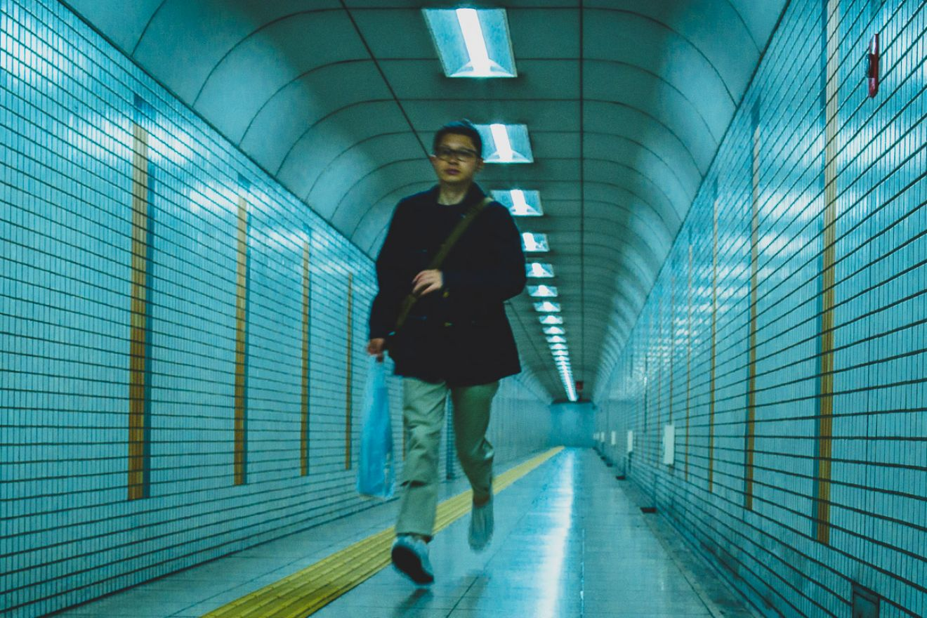 Man running down a metro pedestrian tunnel