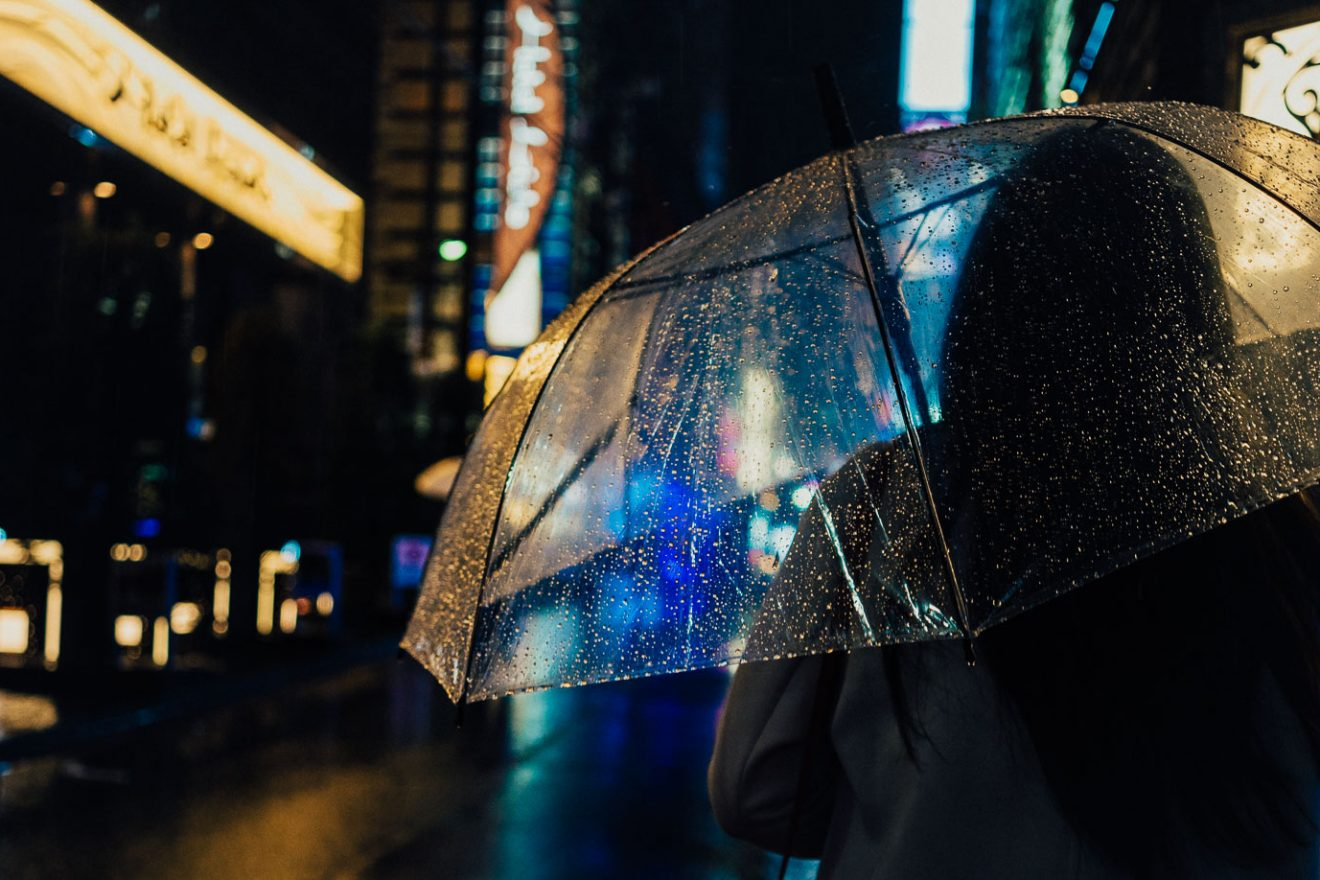 Woman with umbrella walking Tokyo streets at night