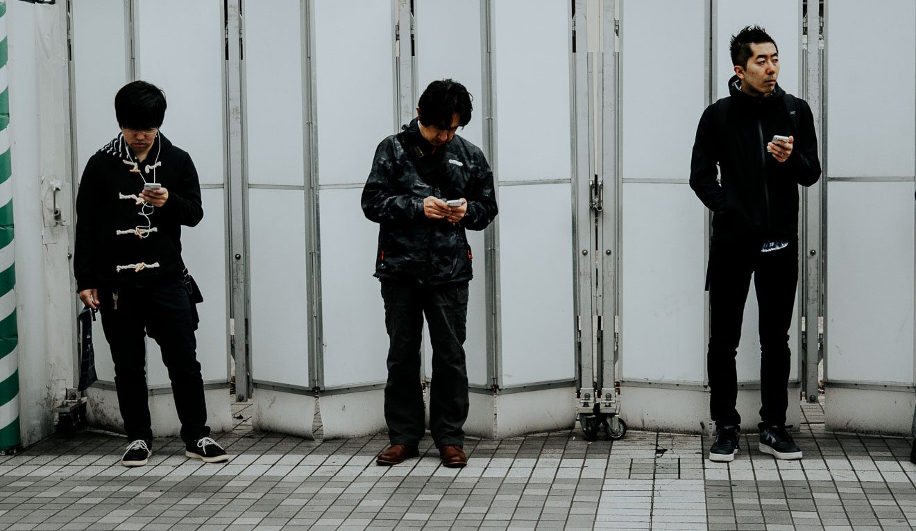 men waiting at bus stop, all with phones