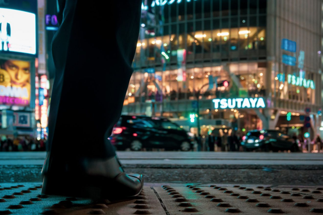 Man before crossing Shibuya Crossing, shoe perspective