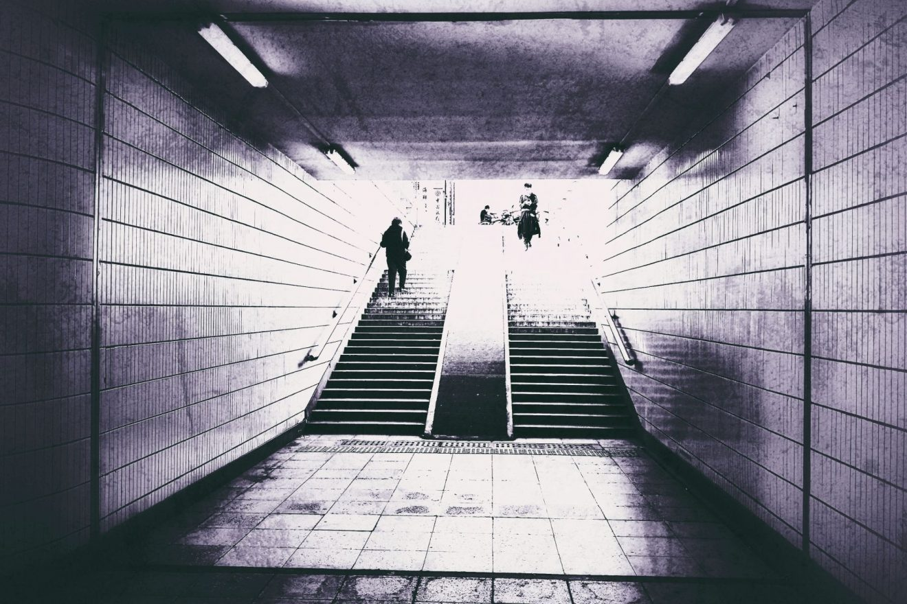 two people down / up the stairs of a metro entrance