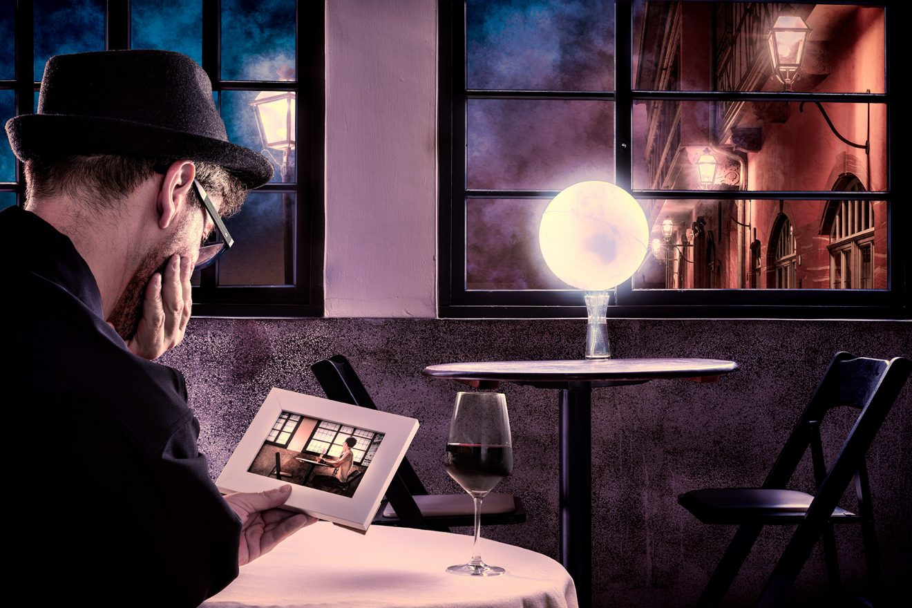 man holding photo in a dark cafe, globe glowing on another table