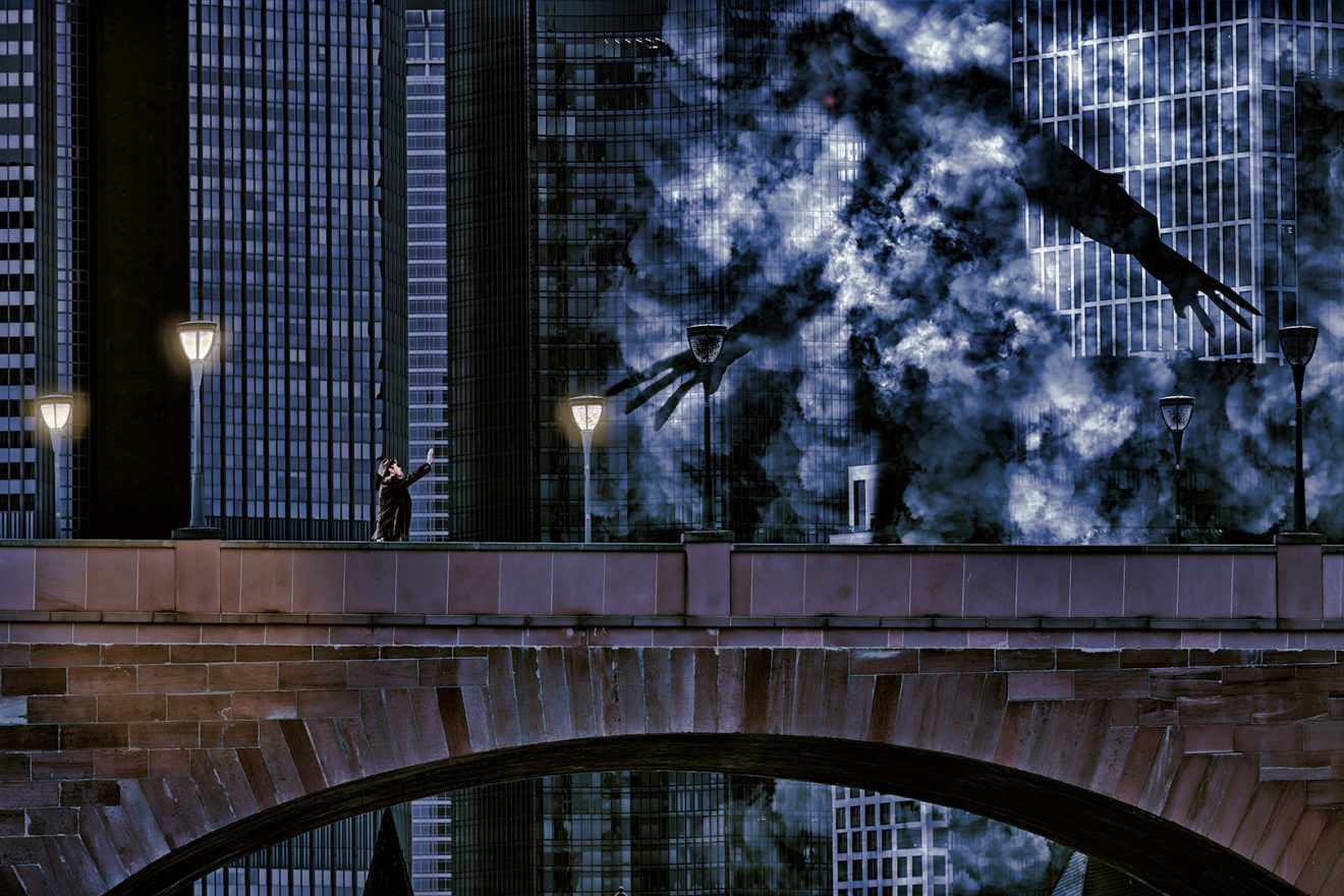 Man standing on bridge holding out to giant dark shadow, skyline in background,